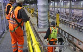 Arbeiter im Bahndepot mit Absauganlage